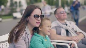 Η νέα μητέρα που κρατά λίγη κόρη παραδίδει επάνω το θερινό πάρκο, συνεδρίαση πατέρων πλησίον απόθεμα βίντεο