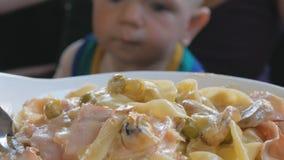 Η νέα μητέρα ταΐζει το μωρό στα ζυμαρικά περιτυλίξεών της στην Ιταλία Το παιδί 1 έτος, αυτό είναι σε μια πράσινη μπλούζα απόθεμα βίντεο