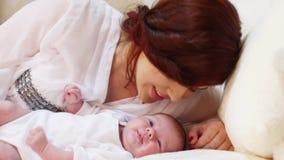 Η νέα μητέρα την φιλά λίγο χαριτωμένο μωρό στο άσπρο κρεβάτι στην κρεβατοκάμαρα απόθεμα βίντεο
