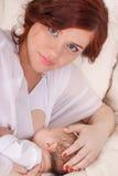 Η νέα μητέρα χαμογελά και ταΐζει το νεογέννητο μωρό της Στοκ Φωτογραφία