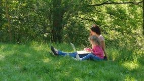 Η νέα μητέρα brunette και η χαριτωμένη κόρη με τη σγουρή ξανθή τρίχα χρησιμοποιούν την άσπρη συνεδρίαση lap-top στην πράσινη χλόη απόθεμα βίντεο