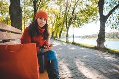 Η νέα μοντέρνη γυναίκα κάθεται στον πάγκο μετά από να ψωνίσει στοκ εικόνες
