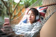 Η νέα μουσική ακούσματος γυναικών με το έξυπνο τηλέφωνο χαλαρώνει να βρεθεί σε μια αιώρα στις διακοπές Στοκ Εικόνα