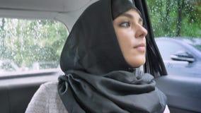 Η νέα μουσουλμανική γυναίκα στο hijab κοιτάζει έξω για τη θέση στο βροχερό παράθυρο στο αυτοκίνητο, έννοια μεταφορών, καιρική ένν απόθεμα βίντεο