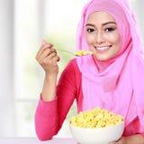 Η νέα μουσουλμανική γυναίκα είχε δημητριακά για το πρόγευμα στοκ φωτογραφίες