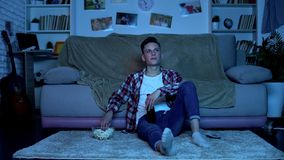 Η νέα μπύρα κατανάλωσης σπουδαστών και κατανάλωση popcorn που προσέχει τη TV παρουσιάζει, ελεύθερος χρόνος Σαββατοκύριακου στοκ εικόνα με δικαίωμα ελεύθερης χρήσης