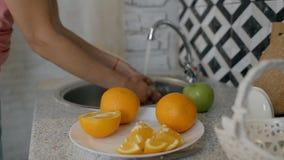 Η νέα νοικοκυρά πλένει το πράσινο μήλο κάτω από τη βρύση, που στέκεται στη σύγχρονη κουζίνα απόθεμα βίντεο
