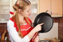 Η νέα νοικοκυρά στην κόκκινη ποδιά με τα αστεία ponytails κρατά το τηγάνισμα π Στοκ Εικόνα
