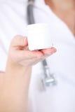 Η νέα νοσοκόμα γιατρών γυναικών κρατά το άσπρο κενό πλαστικό μπουκάλι. Στοκ Εικόνες