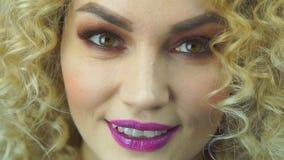 Η νέα ξανθή γυναίκα ανοίγει τα μάτια της και το χαμόγελο με τα ρόδινα χείλια Όμορφη γυναίκα με το επαγγελματικό χαμόγελο makeup φιλμ μικρού μήκους
