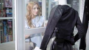 Η νέα ξανθή γυναίκα βλέπει το σακάκι δέρματος στην επίδειξη μπουτίκ ` s απόθεμα βίντεο