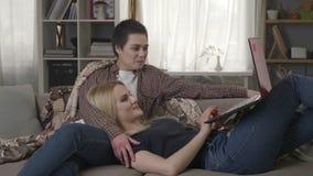Η νέα ξανθή γυναίκα βρίσκεται στην περιτύλιξη ενός brunette και της προσοχής ενός αστείου βίντεο στο lap-top, φίλοι, λεσβίες 60 f απόθεμα βίντεο