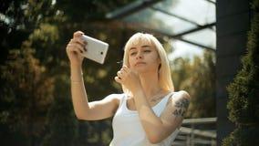 Η νέα ξανθή γυναίκα εξετάζει την αντανάκλαση σε ένα smartphone ισιώνει τις χρήσεις τρίχας της το τηλέφωνο ως καθρέφτη απόθεμα βίντεο