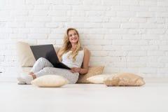 Η νέα ξανθή γυναίκα κάθεται στα μαξιλάρια πατωμάτων χρησιμοποιώντας το φορητό προσωπικό υπολογιστή, το όμορφο ευτυχές χαμόγελο κο Στοκ Εικόνα