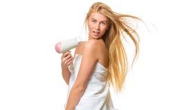 Η νέα ξανθή γυναίκα με τα μπλε μάτια στην πετσέτα ξεραίνει την τρίχα Στοκ Εικόνες