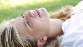 Η νέα ξανθή γυναίκα με τα όμορφα μπλε μάτια βρίσκεται στη χλόη στο πάρκο απόθεμα βίντεο