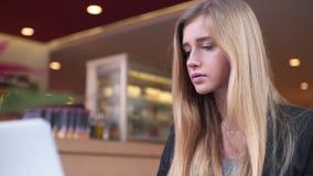 Η νέα ξανθή γυναίκα στο μαύρο σακάκι κάθεται στο κατάστημα καφέδων Πίνει τον καφέ της και εργάζεται με απόθεμα βίντεο