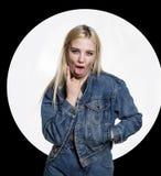Η νέα ξανθή γυναίκα στο τζιν jaket και τα τζιν παρουσιάζει γλώσσα μεταξύ δύο δάχτυλων στο άσπρο υπόβαθρο άσεμνος τρόπος ζωής Στοκ φωτογραφία με δικαίωμα ελεύθερης χρήσης