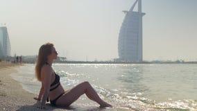 Η νέα ξανθή γυναίκα φορά το μαύρο μπικίνι κάθεται σε μια αμμώδη παραλία στο Ντουμπάι φιλμ μικρού μήκους