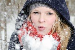 Η νέα ξανθή γυναίκα φυσά σε μια χούφτα του χιονιού Στοκ Φωτογραφίες