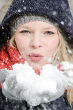 Η νέα ξανθή γυναίκα φυσά σε μια χούφτα του χιονιού Στοκ Φωτογραφία