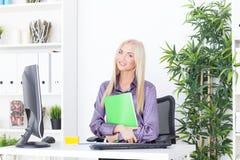 Η νέα ξανθή επιχειρηματίας με το φάκελλο κάθεται στον πίνακα στο γραφείο Στοκ φωτογραφία με δικαίωμα ελεύθερης χρήσης