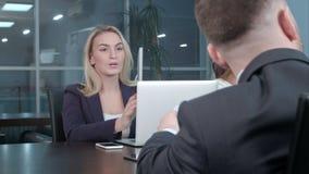 Η νέα ξανθή επιχειρηματίας που εργάζεται επικοινωνεί με τους συναδέλφους στη διάσκεψη στο γραφείο Στοκ Φωτογραφία