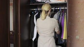 Η νέα ξανθή στάση γυναικών μπροστά από μια ανοιγμένη ντουλάπα στο σπίτι και η επιλογή ντύνουν για να ντύσουν μέσα απόθεμα βίντεο