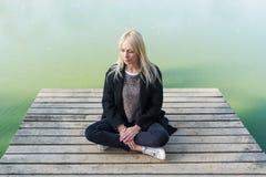 Η νέα ξανθή συνεδρίαση γυναικών θέτει μέσα των lotos στην αποβάθρα το φθινόπωρο στο υπόβαθρο της λίμνης Στοκ εικόνες με δικαίωμα ελεύθερης χρήσης