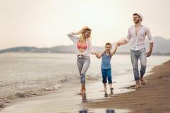 Η νέα οικογένεια έχει τη διασκέδαση στο τρέξιμο και το άλμα παραλιών Στοκ φωτογραφία με δικαίωμα ελεύθερης χρήσης