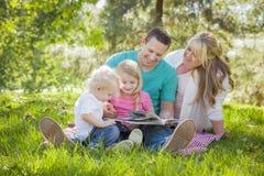 Η νέα οικογένεια απολαμβάνει ένα βιβλίο στο πάρκο στοκ φωτογραφία με δικαίωμα ελεύθερης χρήσης