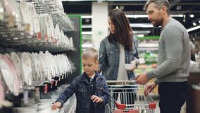 Η νέα οικογένεια επιλέγει τα κύπελλα στην υπεραγορά στο τμήμα σκευών για την κουζίνα, κρατούν τα αγαθά συγκρίνοντας τα και απόθεμα βίντεο