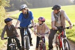 Η νέα οικογένεια θέτει με τα ποδήλατα στο πάρκο Στοκ Φωτογραφίες
