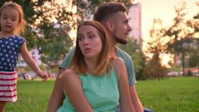 Η νέα οικογένεια κάθεται στην κουβέρτα στο πάρκο το καλοκαίρι, τρεξίματα κορών γύρω από τους γονείς, χαλαρώνει την έννοια απόθεμα βίντεο