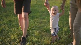 Η νέα οικογένεια περπατά, κρατώντας πρώτα λίγο μωρό παραδώστε κοντά το πράσινο πάρκο φιλμ μικρού μήκους