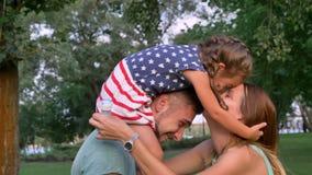 Η νέα οικογένεια περπατά στο πάρκο το καλοκαίρι, το κορίτσι κάθεται στους ώμους πατέρων ` s και αγκαλιάζει τη μητέρα φιλμ μικρού μήκους