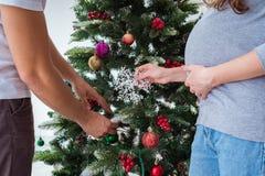 Η νέα οικογένεια που αναμένει τα Χριστούγεννα εορτασμού μωρών παιδιών Στοκ εικόνα με δικαίωμα ελεύθερης χρήσης