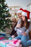 Η νέα οικογένεια που αναμένει τα Χριστούγεννα εορτασμού μωρών παιδιών Στοκ Φωτογραφία