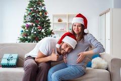 Η νέα οικογένεια που αναμένει τα Χριστούγεννα εορτασμού μωρών παιδιών Στοκ φωτογραφία με δικαίωμα ελεύθερης χρήσης