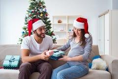 Η νέα οικογένεια που αναμένει τα Χριστούγεννα εορτασμού μωρών παιδιών Στοκ εικόνες με δικαίωμα ελεύθερης χρήσης