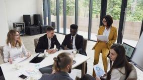 Η νέα ομάδα των multiethnic επιχειρηματιών διευθύνει την ανάλυση των οικονομικών εγγράφων που παρουσιάζουν το εισόδημα, τα διαγρά απόθεμα βίντεο