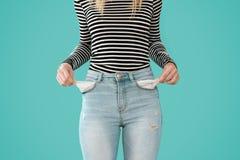 Η νέα παρουσίαση γυναικών όχι δεν έχει τίποτα στις τσέπες τζιν της στο μπλε υπόβαθρο στοκ εικόνες