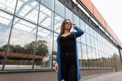 Η νέα προκλητική γυναίκα hipster σε ένα εκλεκτής ποιότητας πλεκτό ακρωτήριο στα καθιερώνοντα τη μόδα γυαλιά ηλίου σε μια μαύρη μο στοκ φωτογραφία με δικαίωμα ελεύθερης χρήσης