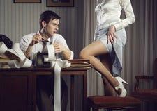 Η νέα προκλητική γυναίκα παρουσιάζει ένα πόδι για τον επιχειρησιακό άνδρα στοκ εικόνες