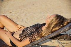 Η νέα προκλητική γυναίκα που τοποθετεί και που μαλακώνεται πλησίον, ενώνει την καλή καυτή ημέρα καλοκαιρινών διακοπών, φορώντας μ στοκ φωτογραφία