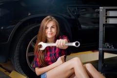 Η νέα προκλητική γυναίκα brunette ως μηχανικός στο ελεγχμένο πουκάμισο παρουσιάζει γαλλικό κλειδί Μακροεντολή θαμπάδων Στοκ Εικόνα