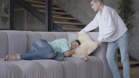 Η νέα πτώση μητέρων κοιμισμένη στο σπίτι Ο γιος εφήβων βάζει το μαξιλάρι κάτω από το κεφάλι γυναικών και βρίσκεται έπειτα κοντά m απόθεμα βίντεο