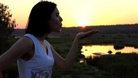 Η νέα ρομαντική γυναίκα στέλνει ένα φιλί αέρα στο ηλιοβασίλεμα της Νίκαιας σε σε αργή κίνηση φιλμ μικρού μήκους
