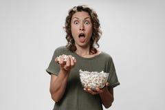 Η νέα σγουρή γυναίκα ανοίγει τα μάτια και το στόμα τρώγοντας ευρέως popcorn, προσέχοντας έναν κινηματογράφο ή μια TV στοκ φωτογραφίες με δικαίωμα ελεύθερης χρήσης
