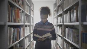 Η νέα σγουρή γυναίκα αφροαμερικάνων διαβάζει το βιβλίο περπατώντας μεταξύ των ραφιών στη βιβλιοθήκη απόθεμα βίντεο